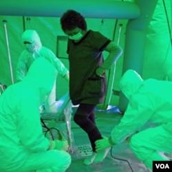 Star medis memindai seorang perempuan untuk mendeteksi kemungkinan radiasi di tubuhnya, setelah ia dievakuasi dari sebuah daerah berjarak 20 kilometer dari PLTN, Rabu (16/3).