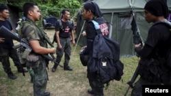 말레이시아 북부 태국 접경지역인 왕켈리안에서 특수부대원들이 경찰과 이야기하고 있다. 말레이시아 경찰은 이민자들의 것으로 보이는 139개의 무덤을 발견했다.