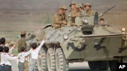 FILE - Afghan children and a soldier bid farewell to Soviet soldiers riding atop an armored personnel carrier as the official troop withdrawal begins after years of military intervention in war-torn Afghanistan on May 15, 1988, in Kabul.