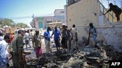 Une foule regarde l'épave d'une voiture après l'explosion d'une bombe à lextérieur du ministère de l'Education à Mogadiscio, le 14 avril 2015.