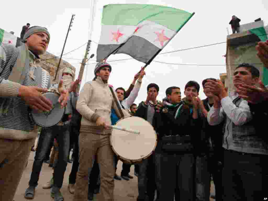 Anti-Syrian regime protesters play drums and wave a revolutionary flag during a demonstration in Idlib, Syria, on February 6, 2012. (AP)