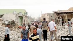 Cư dân đứng giữa đống đổ nát tại hiện trường vụ nổ ở thị trấn Tuz Khormato, miền bắc Iraq, ngày 21/5/2013.