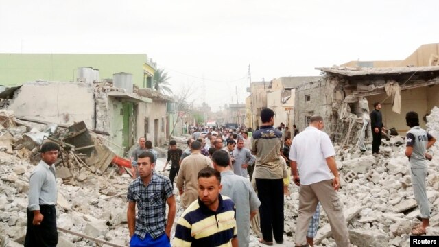 Residents stand amid rubble at blast scene in Tuz Khormato town in northern Iraq, May 21, 2013.
