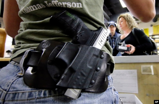 FILE - Kayla Brown, left, wears her gun on her hip while working at the Spring Guns and Ammo store in Spring, Texas, JAN. 4, 2016.