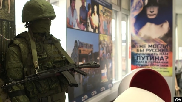 """A mannequin soldier holding a rifle and representing the """"little green men"""" whom Russia dispatched to help annex Ukraine's Crimea overlooks the office of pro-Kremlin youth group SET (Network). (VOA video screengrab)"""