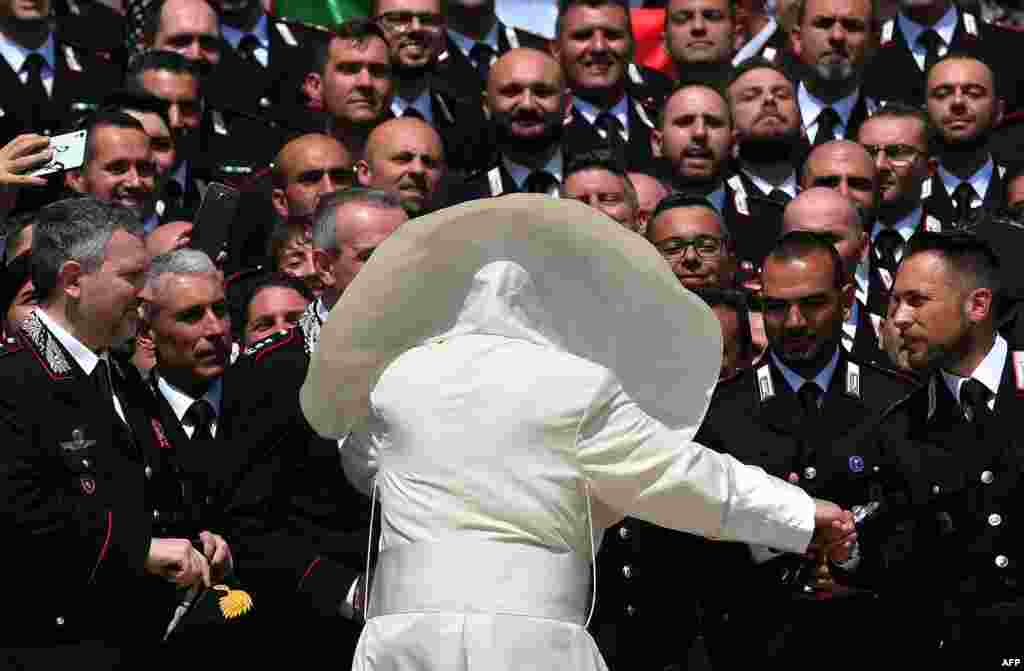 A wind blows Pope Francis' mantle as he meets the Carabinieri during the general audience in Saint Peter's Square at the Vatican.