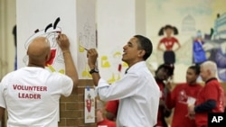 President Barack Obama helps to paint cartoon characters in a lunchroom as he observes the Martin Luther King Jr. Day holiday, 17 Jan 2011