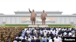 FILE - People and soldiers gather to offer flowers to the statues of state founder Kim Il Sung and former leader Kim Jong Il on the Day of Songun at Mansu hill, Pyongyang, North Korea, in this undated photo released by North Korea's Korean Central News Ag