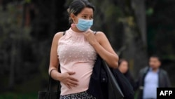 A pregnant woman wears a face mask as a preventive measure against the spread of the new coronavirus, COVID-19, as she waits for the bus in Bogota, on March 16, 2020.