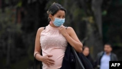 A pregnant woman wears a face mask as a preventive measure against the spread of the new coronavirus, COVID-19, as she waits for the bus in Bogota, on March 16, 2020. - The Colombian government announced the indefinite suspension of face-to-face classes i