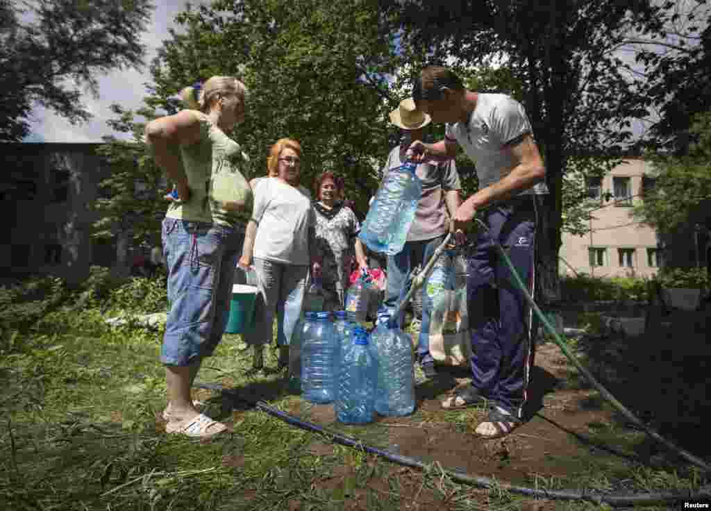 Residents collect water at a pumping station in the eastern Ukranian city of Slovyansk, June 17, 2014.