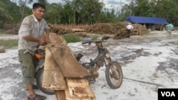 A villager tying timber to his motorcycle for trading with the logging company as two UN investigators are looking around in the compound of the logging company, April 27, 2012.