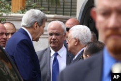 U.S. Secretary of State John Kerry, center left, speaks with Palestinian President Mahmoud Abbas, center right, and Abbas aide Saeb Erekat, center, after their meeting at Abbas' residence in Amman, Jordan, Oct. 24, 2015.