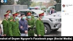 Cảnh sát áp giải một bị cáo trong vụ Đồng Tâm ra tòa; ảnh trên Facebook của chị Nguyễn Thị Duyên, 8/3/2021.