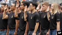 FILE - New Army recruits take part in a swearing in ceremony before a baseball game between the San Diego Padres and the Colorado Rockies Sunday, June 4, 2017, in San Diego. (AP Photo/Gregory Bull)