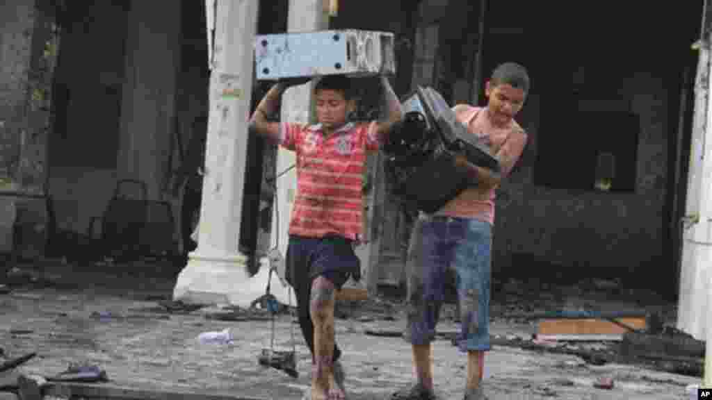 Egyptian children carry computer equipment in the burned remains of the Rabaah al-Adawiya mosque, in the center of the largest protest camp of supporters of ousted President Morsi,