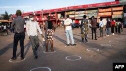 Bato bazali kotosa mokano ya kokabwana na baninga na metre moko liboso ya ba magasins na Kigali, Rwanda, 4 mai 2020.