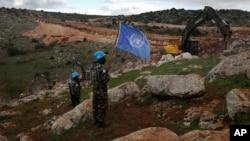 Pasukan penjaga perdamaian PBB memegang bendera sambil mengamati alat berat Israel mencoba menghancurkan terowongan yang dibangun Hizbullah dekat perbatasan Lebanon-Israel di Desa Mays al-Jabal, 13 Desember 2018.