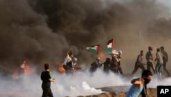 فلسطینی مظاہرین کو منتشر کرنے کے لیے اسرائیلی فورسز اشک آور گیس کے گولے پھینک رہی ہے جب کہ مظاہرین کے جلائے ہوئے ٹائروں سے گہرا دھواں اٹھ رہا ہے۔ 7 ستمبر 2018