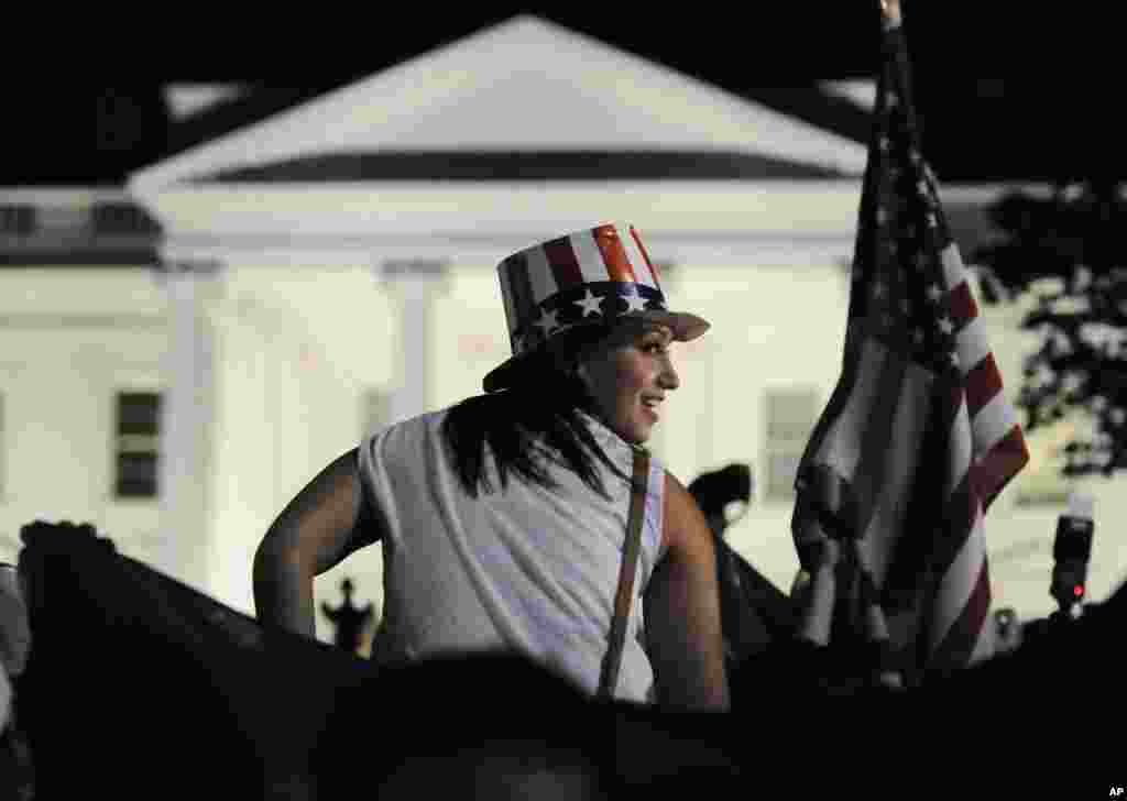 A woman sits on a reveler's shoulders outside the gates of the White House after U.S. President Barack Obama announced that U.S. authorities have recovered the dead body of al-Qaida leader Osama bin Laden, May 1, 2011 (Reuters)