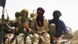 Fighters from the Islamist group Ansar Dine stand guard during the handover of a Swiss female hostage for transport by helicopter to neighboring Burkina Faso in the desert outside Timbuktu, Mali, April 24, 2012.