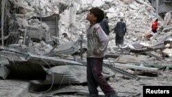 (資料照片:阿勒頗反政府力量控制區一個男孩凝視著空襲後的廢墟)