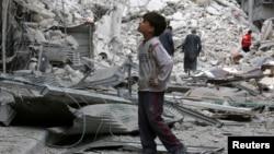 资料照片:阿勒颇反政府力量控制区一个男孩凝视着空袭后的废墟