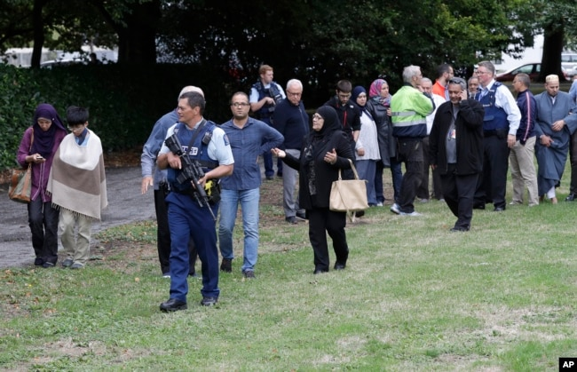 Police escort witnesses away from a mosque in central Christchurch, New Zealand, Friday, March 15, 2019.