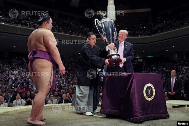 El presidente de EE.UU., Donald Trump, se prepara para entregar la Copa del Presidente al luchador de sumo Asanoyama, ganador del Gran Torneo de Sumo de Verano en el Ryogoku Kokigikan Sumo Hall, en Tokio. Mayo 26, de 2019.