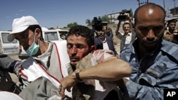 Anti-government protesters carry a wounded protester from the site of clashes with security forces, in Sana'a, Yemen, October 15, 2011.