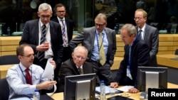 Bộ trưởng Tài chính Đức Wolfgang Schaeuble (giữa) nói chuyện với các giới chức trong cuộc họp của các bộ trưởng tài chính khu vực đồng euro về tình hình ở Hy Lạp tại Brussels, Bỉ, 12/7/2015.