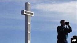 游人在有争议十字架战争纪念碑前摄影