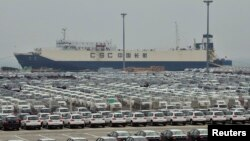 FILE - Newly-manufactured cars and a container ship are seen at Dayaowan port of Dalian, Liaoning province, June 10, 2012.
