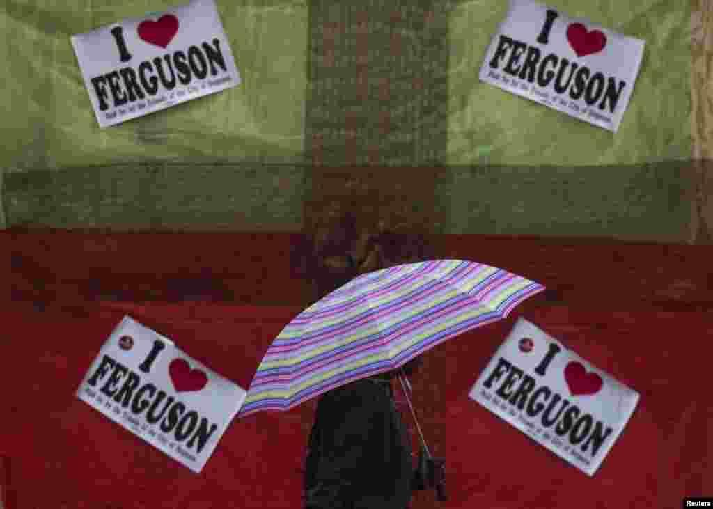 Cư dân đi ngang qua một cửa hàng bị bỏ hoang ở Ferguson với các khẩu hiệu ủng hộ Michael Brown.