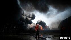 Un bombero participa en los intentos por apagar un incendio en la planta de electricidad de Gaza, alcanzada por los bombardeos irsraelíes de este martes.