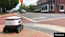 A Starship delivery robot waits to cross an intersection as it drives itself to deliver food amid the coronavirus disease (COVID-19) outbreak in Fairfax, Virginia, U.S., May 15, 2020. (REUTERS/Julio-Cesar Chavez)