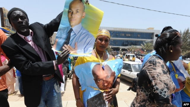 Members and supporters of the Parti Democratique Senegalais (PDS) hold a poster showing their leader, former Senegalese president Abdoulaye Wade and his son Karim, as they rally in front of the party's headquarters in Dakar, Apr. 23, 2014.