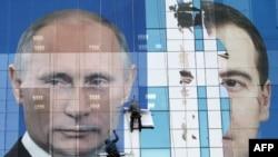 Các công nhân đang gắn tấm quảng cáo, trước bầu cử, hình Tổng thống Nga Medvedev (phải) và Thủ tướng Putin, kêu gọi dân chúng bỏ phiếu cho đảng 'Nước Nga Thống nhất'