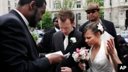 Bishop Harry R. Jackson Jr. of Beltsville, Md., left, prays with Jonathan Paul Ganucheau, 24, and Denise Buckbinder Ganucheau, 26, both of Dallas, Texas, before performing a religious wedding ceremony in Washington, May 5, 2009.