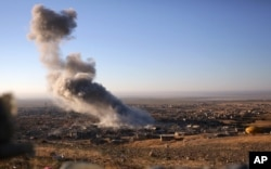 Smoke believed to be from an airstrike billows over the northern Iraqi town of Sinjar, Nov. 12, 2015.