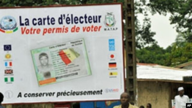 People walk in front of posters for the presidential elections and instructions on the voting card, Conakry, 25 Jun 2010
