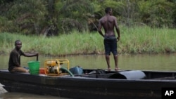 Suspected oil thieves ride a wooden boat full of stolen crude oil on the creeks of Bayelsa, Nigeria, May 18, 2013.