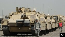 U.S. soldiers walk past tanks at a courtyard at Camp Liberty in Baghdad. U.S troops are scheduled to pull out of the country by the end of this year, according to a 2008 security pact between the U.S. and Iraq. (File September 30, 2011).