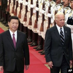 Chinese Vice President Xi Jinping, left, accompanies his U.S. counterpart Joseph Biden to review an honor guard during a welcoming ceremony inside the Great Hall of the People in Beijing, August 18, 2011