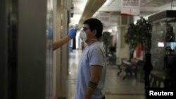 Seorang pekerja memeriksa tubuh pengunjung sebagai tindakan pencegahan di tengah persiapan pembukaan kembali pusat bisnis menyusul pandemi virus corona di Santiago, Chili, 29 April 2020. (Foto: Reuters)