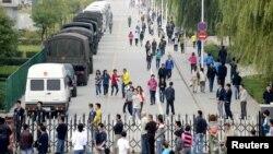 Trabajadores pasan cerca de un retén miliar a la entrada de la fábrica de Foxconn, en Taiyuan, provincia de Shanxi, el 24 de septiembre de 2012.