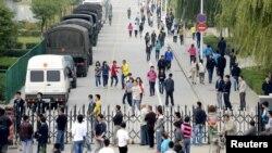 Công nhân đi bộ qua các xe cảnh sát gần lối vào Khu Công nghiệp Foxconn ở Thái Nguyên, tỉnh Sơn Tây, Trung Quốc, ngày 24/9/2012