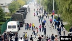 Para pekerja melewati beberapa mobil polisi yang berjaga di sekitar pabrik Foxconn di Taiyuan, provinsi Shanxi, Tiongkok (24/9). Pabrik pemasok iPhone Apple itu menghentikan produksinya pasca bentrokan antar karyawan di asramanya, yang melibatkan 2.000 pekerja dan mencederai 40 orang.