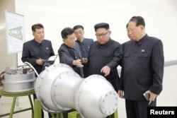 North Korean leader Kim Jong Un, center, with a device said to be a nuclear weapon in this undated photo released by North Korea's Korean Central News Agency (KCNA) in Pyongyang, Sept. 3, 2017. (KCNA via REUTERS)