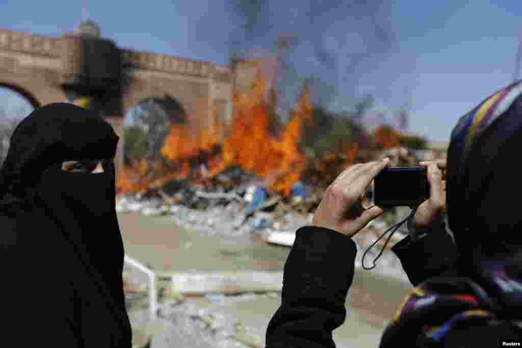 A woman takes a photo of a fire that was set to demolished huts at Taghyeer (Change) Square, where pro-democracy protesters had camped to demand a regime change in 2011, in Sana'a.